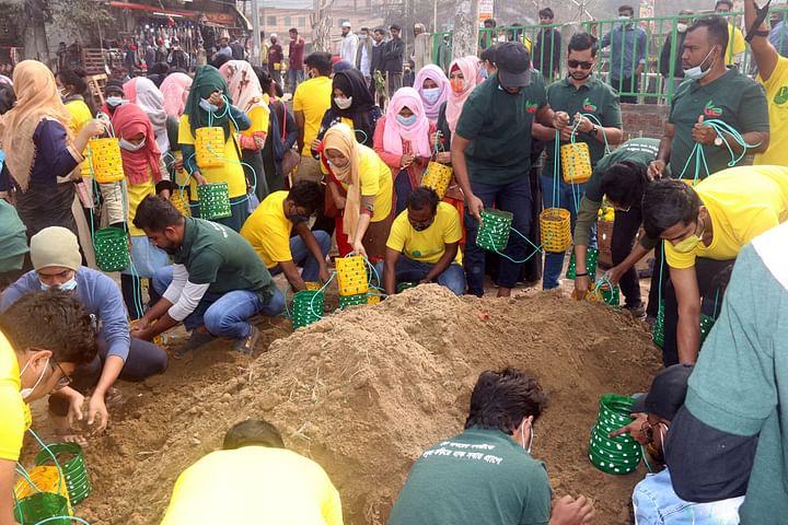 রঙিন প্লাস্টিকের বোতলে মাটি ভরে তৈরি করা হচ্ছে টব