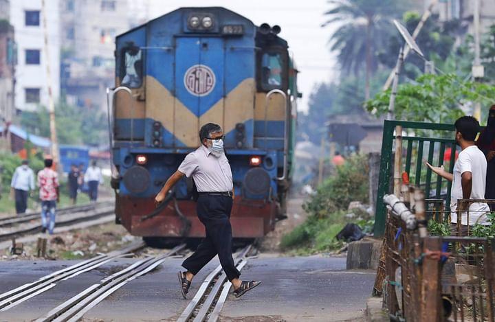 আসছে ট্রেন, কিন্তু পারাপারের জন্য যেন তর সইছে না এই পথচারীর। গত ৩ নভেম্বর রাজধানীর মগবাজারে
