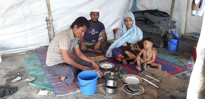 কক্সবাজারের উখিয়ার বালুখালী ক্যাম্পে বাইরে থেকে কিনে আনা খাবার খাচ্ছে একটি রোহিঙ্গা পরিবার