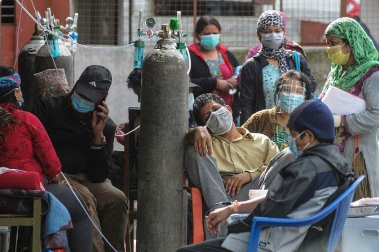 হাসপাতালের বাইরে এভাবেই অক্সিজেন নিতে দেখা যায় কোভিড রোগীদের। কাঠমান্ডু, নেপাল, ১৩ মে