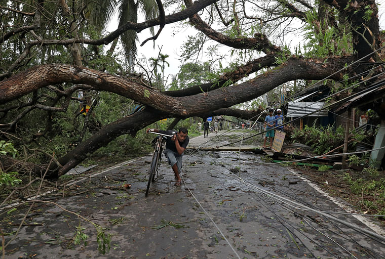 A man walks with his bicycle under an uprooted tree after Cyclone Amphan made its landfall, in South 24 Parganas district.