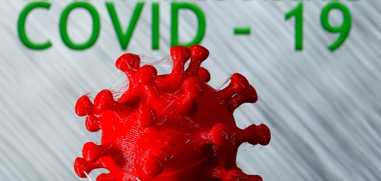 A 3D-printed coronavirus model in front of the words coronavirus disease (COVID-19) on display in this illustration taken on 25 March