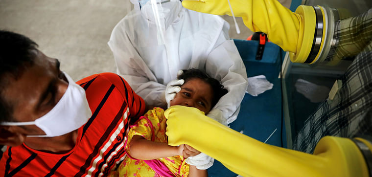 A health worker collects a swab sample from a child at Mugda Medical College and Hospital, as the coronavirus disease (COVID-19) outbreak continues, in Dhaka, Bangladesh, on 23 June 2020