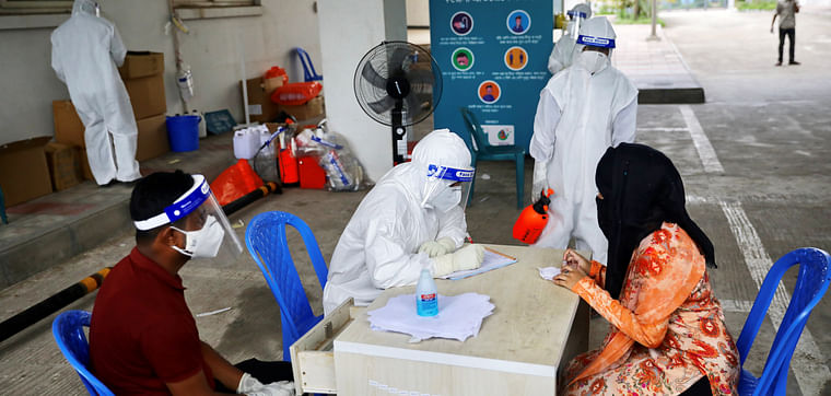 A woman consults a doctor before swab testing at Mugda Medical College and Hospital, as the coronavirus disease (COVID-19) outbreak continues, in Dhaka, Bangladesh, on 23 June 2020