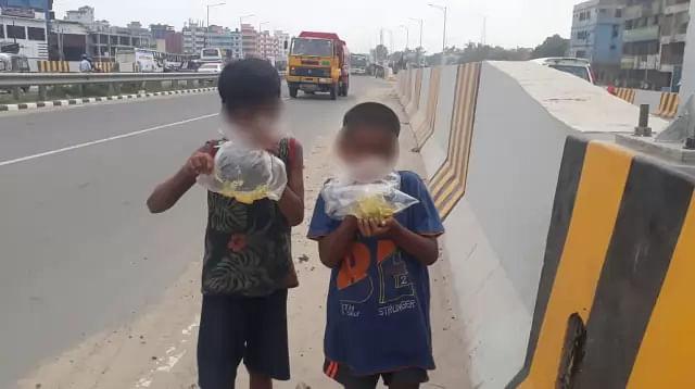 Two small children inhaling 'dandi' on the Dhaka -Mawa highway
