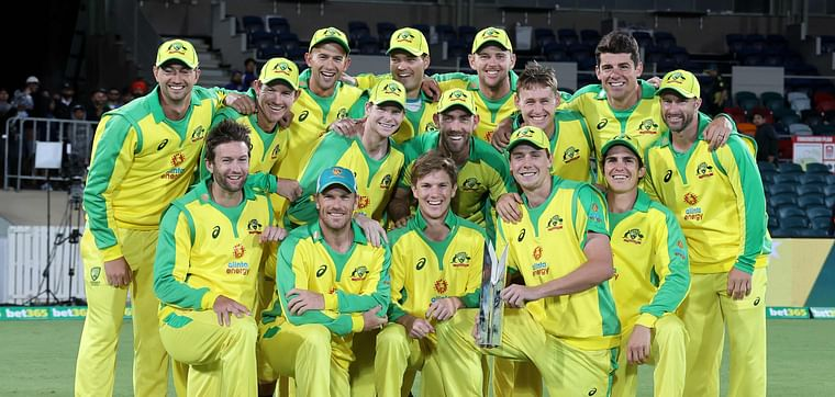 Australian team pose for pictures with the winning trophy of the one-day international cricket series against India at Manuka Oval in Canberra on 2 December 2020