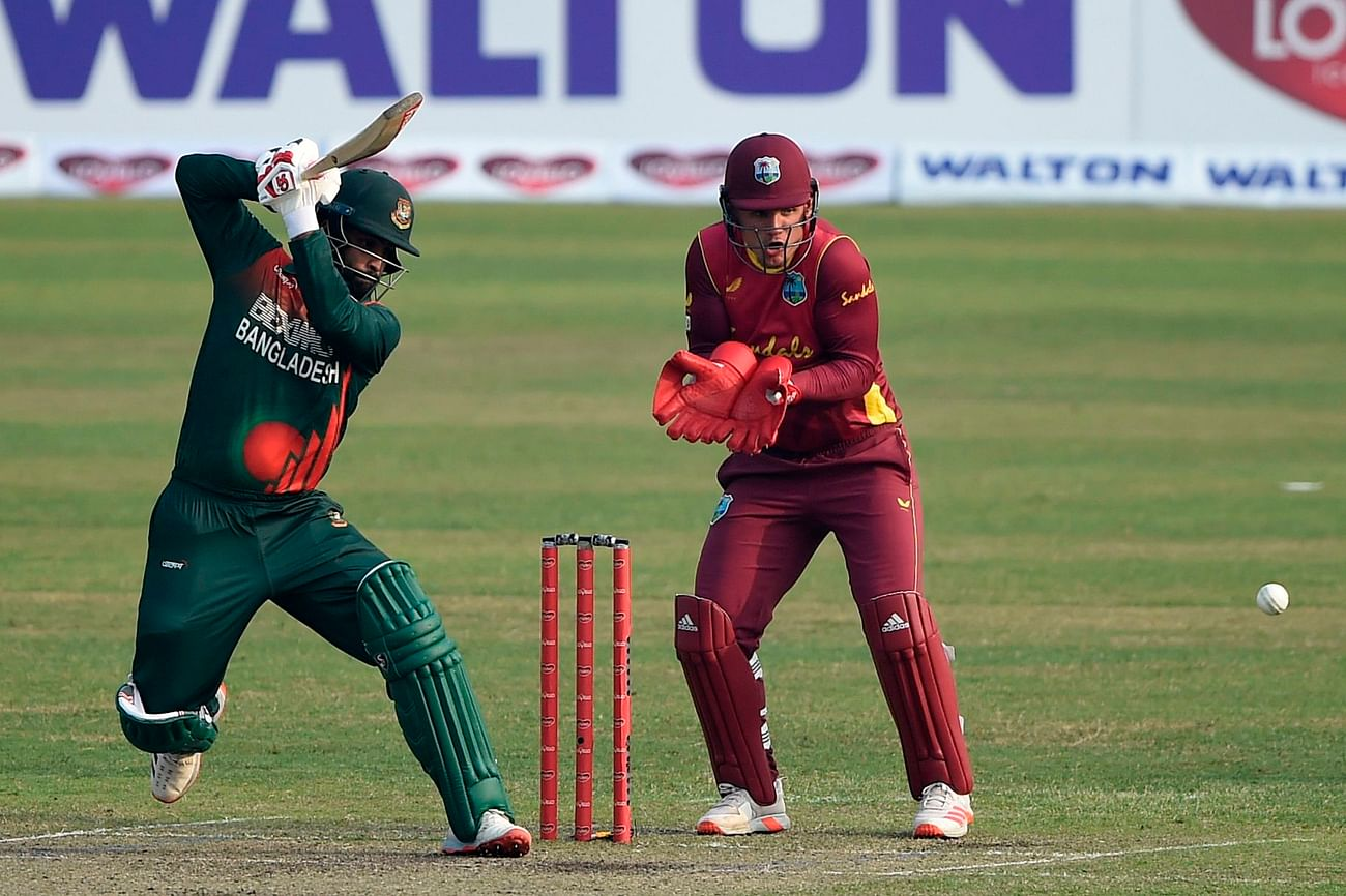 Bangladesh's captain Tamim Iqbal (L) plays a shot as West Indies' wicketkeeper Joshua Da Silva watches during the second one-day international (ODI) cricket match between Bangladesh and West Indies at the Sher-e-Bangla National Cricket Stadium in Dhaka on 22 January, 2021