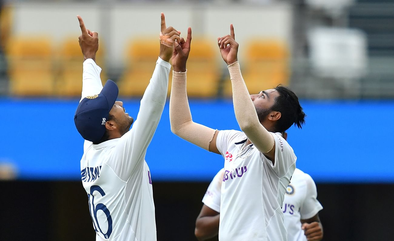 Mohammed Siraj of India celebrates with Mayank Agarwal after getting the wicket of Josh Hazlewood of Australia during day four of the fourth test match between Australia and India at the Gabba in Brisbane, Australia, 18 January, 2021