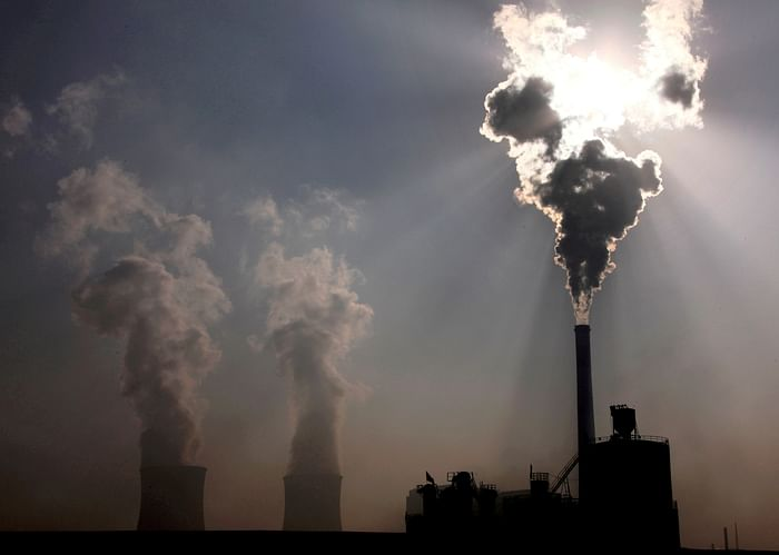 A coal-burning power plant can be seen behind a factory in China's Inner Mongolia Autonomous Region