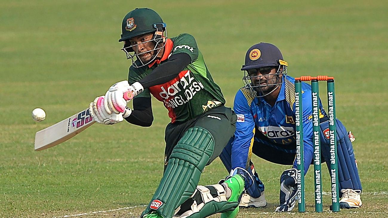Bangladesh's wicketkeeper Mushfiqur Rahim (L) plays a shot as Sri Lanka's captain Kusal Perera looks on during the first one-day international (ODI) cricket match between Sri Lanka and Bangladesh at the Sher-e-Bangla National Cricket Stadium in Dhaka on 23 May 2021