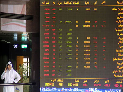 A Kuwaiti trader follows the stock market activity at the Kuwait Stock Exchange (KSE) in Kuwait City.