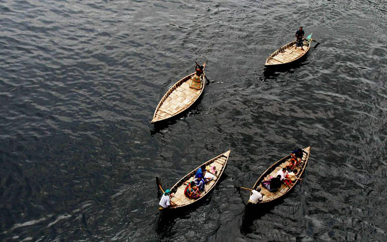 Boats sail on pitch black Buriganga river water polluted by industrial wastes. Photo taken in Babubazar bridge area of city by Saddam Hossain.