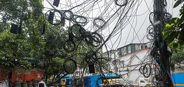 A 10 July 2020 photo shows jungle of twisted cables hanging from an electric pole by Shahid Tazuddin Ahmed Sarani in Dhaka, increasing risk of accidents